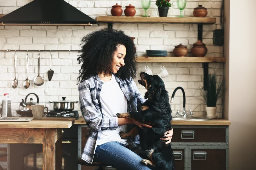 Woman with dog in kitchen