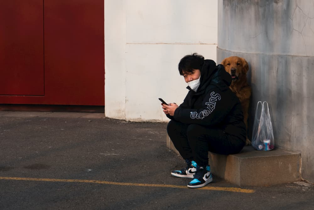 Man sits with dog in Beijing