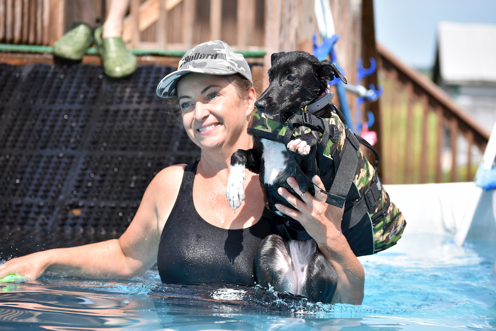 Happy owner in a pool praising dog for swimming