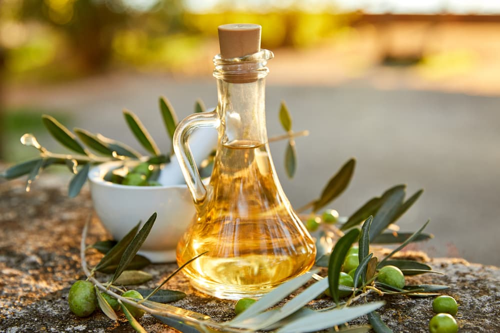 Olive oil bottle next to fresh olives at sunset
