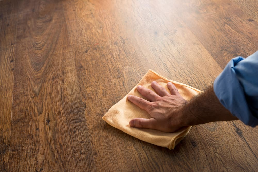 Man cleaning wood floor with cloth