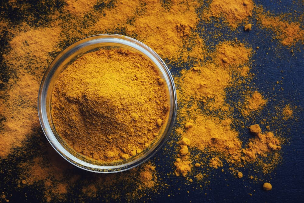 Turmeric powder in a bowl on the table