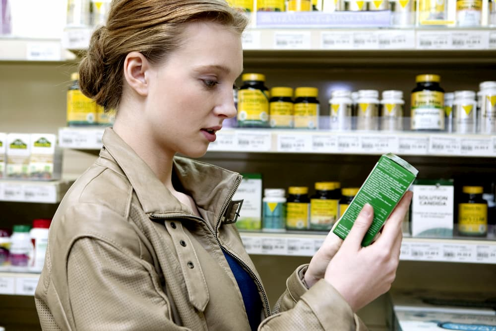 Woman reading label in a health food store