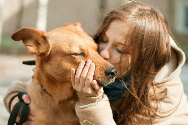 Woman hugging her red dog