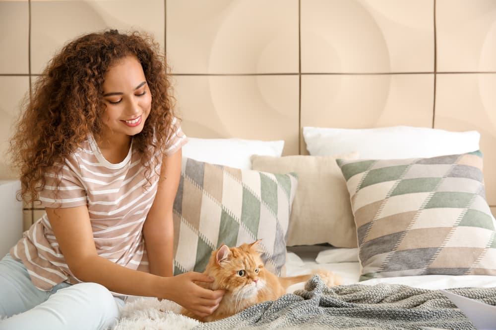 Woman with cat on bed