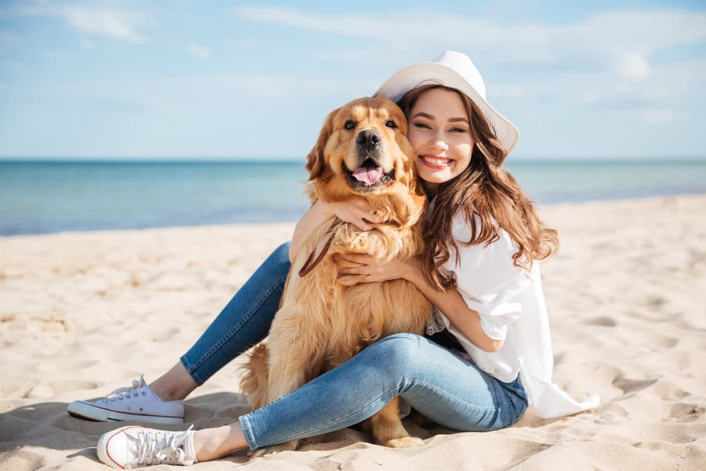 Woman sitting on the beach with her dog