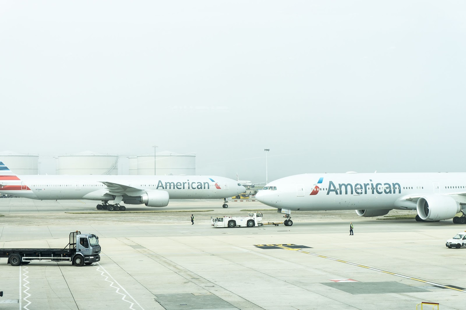 Two American airlines planes sit at the airport landing strip