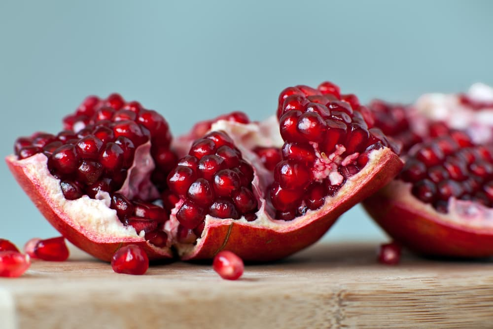 Fresh pomegranate sitting open on a table