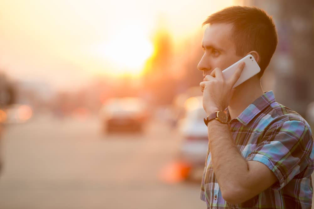 Man talking on phone on a busy street