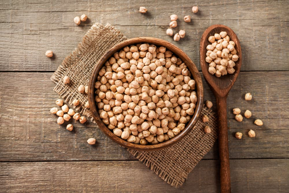 Bowl of chickpeas with spoon on wooden board