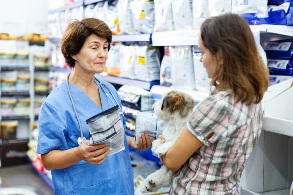 Woman at the shop holding dog talking to vet about dog food